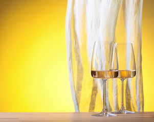 Glasses of white wine on a yellow background.