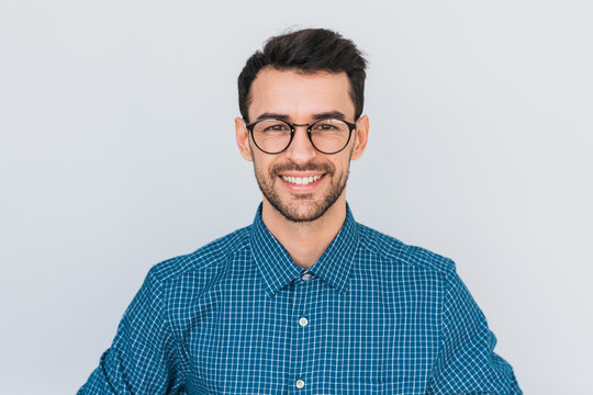 Closeup portrait of handsome smart-looking smiling with toothy smile male posing for social advertisement, isolated on white background with copy space for your promotional information or content.