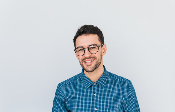 Portrait of handsome smart-looking smiling male posing for social advertisement wearing blue shirt and glasses, isolated on white background with copy space for your promotional information or content