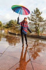 Young woman with rainbow umbrella walking outdoor in the park at a rainy day