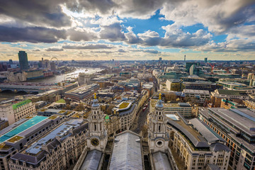 London, England - Panoramic skyline view of London taken from St. Paul's Cathedral with iconic red double-decker buses and beautiful sky and clouds