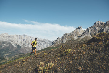 Trail runner running uphill in Picos de Europa Natural Park, Leon, Spain