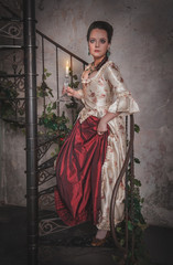Beautiful woman in old historic medieval dress with candle