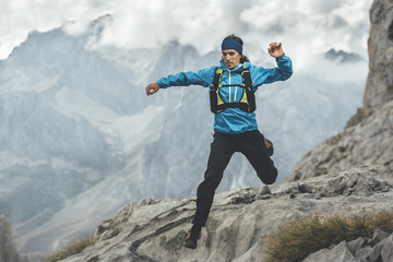 Trail runner jumping over a rocky path in Picos de Europa Natural Park in a rainy day, Asturias, Spain