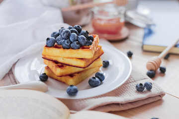Belgian waffles with blueberries on the light wooden table. Healthy breakfast.