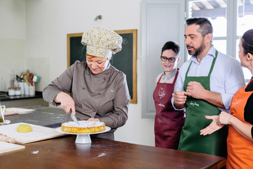 Chef cutting cake at the end of a cooking class in Italy