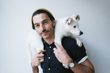 Studio portrait of a handsome guy holding his dog