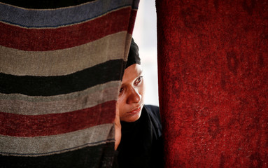 A woman stands behind a curtain inside a temporary shelter after a fire broke out in a Rohingya camp in New Delhi