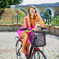 Beautiful girl in pink dress on a bicycle