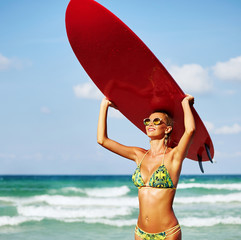 Woman with surfboard on the beach - close up portrait