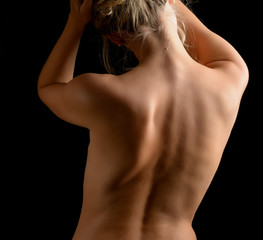 Back view of a caucasian woman on dark background.