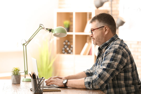 Mature man working with laptop indoors