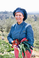 Portrait of happy female chef outdoor holding fresh vegetables from her garden