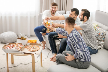 Young men drinking beer and eating pizza while playing video games at home