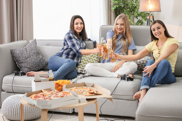 Young women drinking beer while playing video games at home