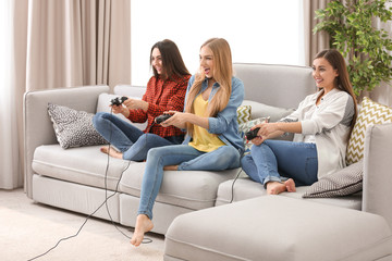 Young women playing video games at home