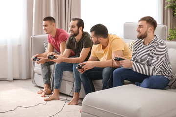 Young men playing video games at home