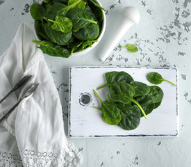 green spinach leaves on a white wooden board