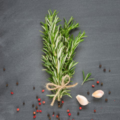 Bunch of rosemary with garlic and spices on chalk board