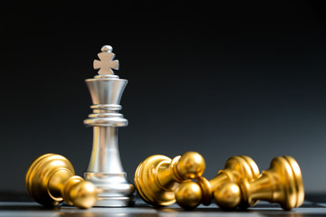 Silver king chess piece win over lying down gold pawn on black background