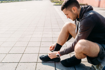 young man tying his shoelace outdoor preparing for training - sport, healthy lifestyle, preparation concept