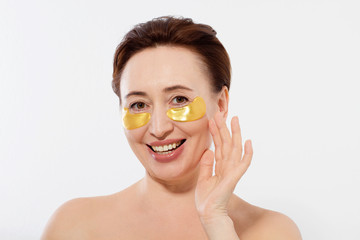 Beauty portrait of middle age woman with wrinkles and a gold patch under eye isolated on white background. Collagen mask and spa concept. Copy space. Summer skin care