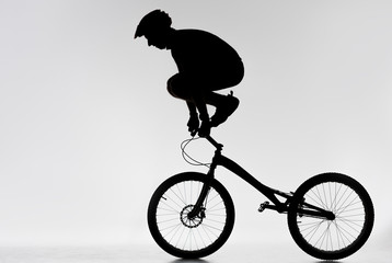 silhouette of trial biker standing on handlebars with hands on white