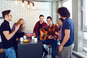 A group of young people having fun playing guitar sing songs at a meeting of friends.