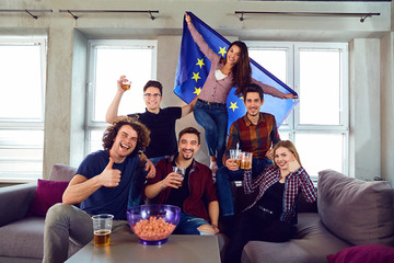A group of friends with a European flag at a party. Friends with cup of beer celebrate the day of Europe.