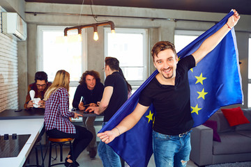 Young man with the european flag in his hands on the background of friends in the room.
