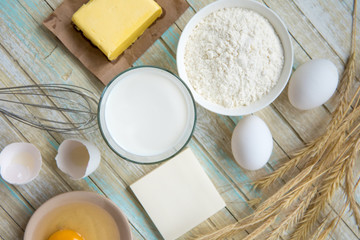 Ingredients for baking: milk, flour, egg and butter top view