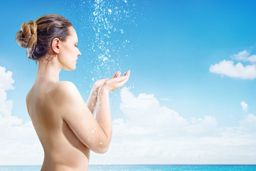 Young woman have shower on the tropical beach