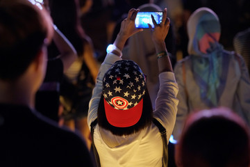 A fan wearing a cap in the colors of Captain America takes a photo at a fan event for Marvel Studio's Avengers: Infinity War movie, in Singapore