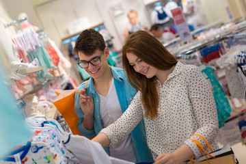 Young couple shopping baby clothes