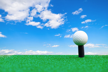 Golf ball on the green grass with blue sky background and copy space.