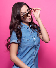 Colorful studio portrait of a young woman surprised looking at something over sunglasses