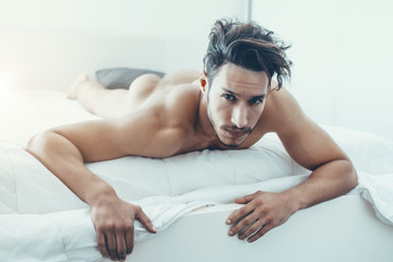 sexy and naked muscular young man sits on a bed in the room Wall mural