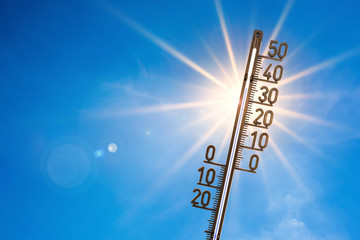 Summer background, bright sun with thermometer