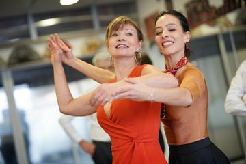 Dance teacher showing senior woman correct gesture