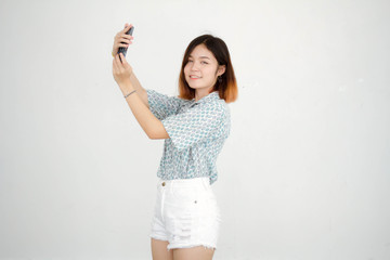 Portrait of thai adult beautiful girl short hair using her smart phone Selfie