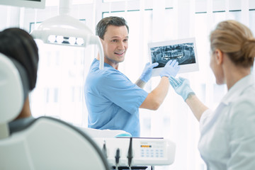 Great results. Content skilled dentist talking with his colleague and showing teeth on the screen