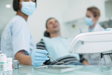 Our routine work. Determined skilled dentist holding an instrument and the patient sitting in the chair