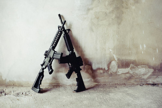 Rifle guns on grunge wall in abandoned house. Terrorist and Soldier concept. Robber and Police concept. War machine gun theme.