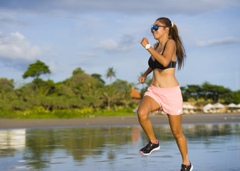 young attractive Asian Chinese sport runner woman in running beach workout on a sunset Summer evening in beautiful sea and coast background