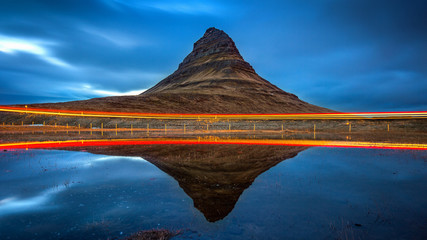 Kirkjufell mountains and reflection with car light, Iceland.