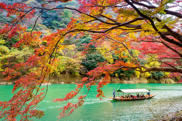 Fototapete - Boatman punting the boat at river. Arashiyama in autumn season along the river in Kyoto, Japan.