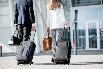Business couple walking together to the airport entrance carrying suitcases and bags