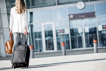 Business woman walking together to the airport entrance carrying suitcases and bags