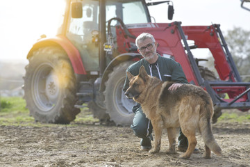 Farmer petting dog outside the barn, tractor in background