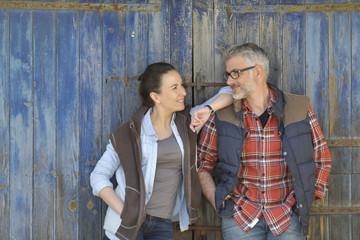 Couple of farmers standing in front of barn wooden door